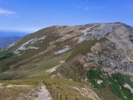 Subida por la arista noroeste del Mostallar. Enfrente, el Penalonga. La valla metálica separa Galicia de León.
